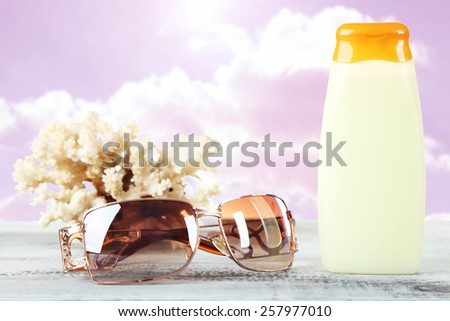 Bottle of suntan cream with sunglasses and coral on table isolated on white - stock photo