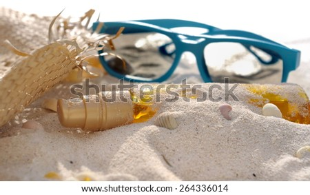 bottle of suntan oil covered by sand with hat and sunglasses - stock photo
