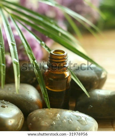Bottle of  tropical  oil and stones.