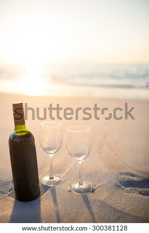 bottle of vine with two glass on the beach