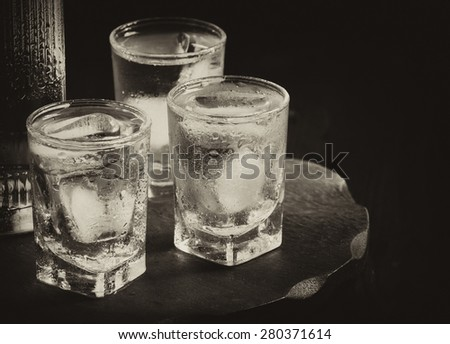 Bottle of vodka and glasses full of ice, the concept of alcohol dependence, selective focus - stock photo