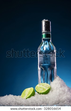 Bottle of vodka and two lime halves with water droplets on a surface in cold ice on blue gradient background. Focus on a bottle. - stock photo