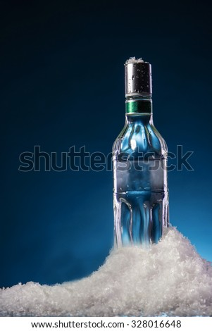 Bottle of vodka with water droplets on a surface in cold ice on blue gradient background. Focus on a bottle. - stock photo