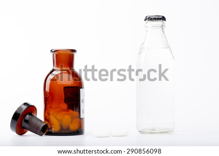 Bottle of water, a glass medicine bottle and white pills on white background - stock photo