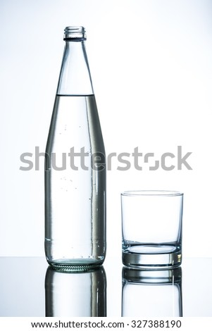 bottle of water and empty glass on glass table - stock photo