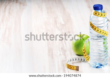 Bottle of water and green apple. Healthy diet concept - stock photo