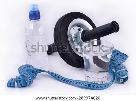 Bottle of water, glass of water, roller wheel for abdominals and measuring tape on white