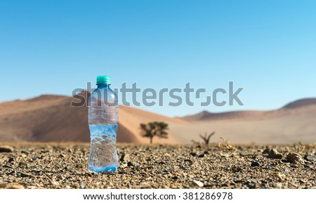 Bottle of water in the middle of the Desert (low angle shot) with dunes in the background - stock photo