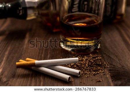 Bottle of whiskey and a glass with cigarettes on a wooden table. Focus on the tobacco