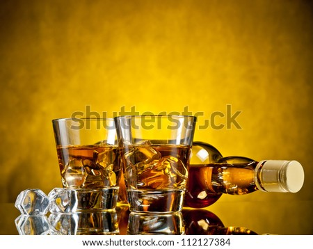 Bottle of whiskey and two whiskeys on the rocks - stock photo