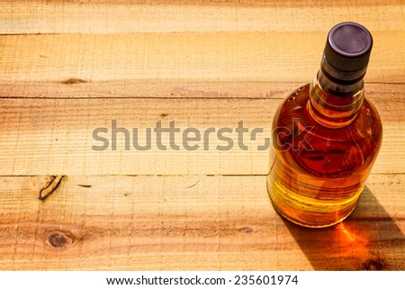 bottle  of whiskey  on a wooden background - stock photo