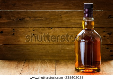 bottle  of whiskey  on a wooden background made with vintage tones - stock photo
