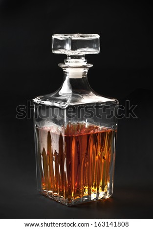 bottle of whiskey on dark background - stock photo