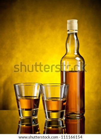 Bottle of whiskey with two filled glasses on yellow grunge background - stock photo