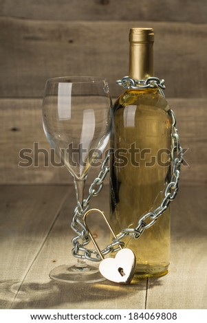 Bottle of white wine and a glass shackled love chain with a lock.