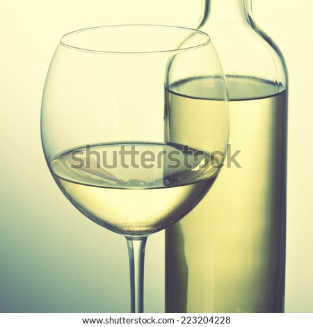 Bottle of white wine and glass. Instagram style filtred image - stock photo