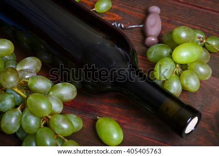 Bottle of white wine, grape and corkscrew on wooden table