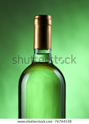 Bottle of white wine on green background
