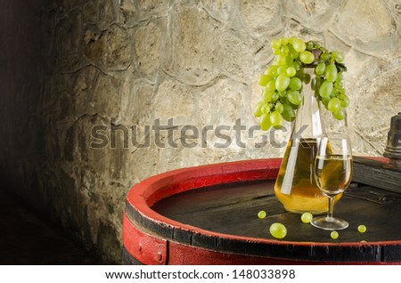 Bottle of white wine, wine glass and white grapes on barrel - stock photo