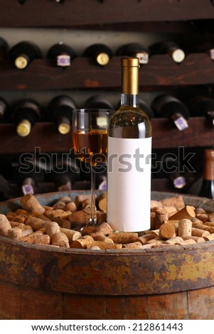 Bottle of white wine with blank label template and glass standing in a wine cellar on a wood barrel