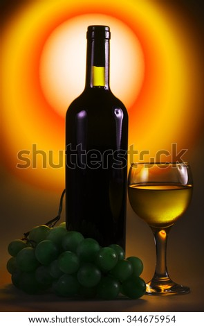 Bottle of white wine with glass and grapes - stock photo