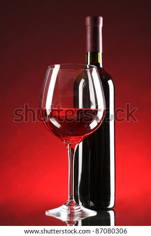 bottle of wine and glasses on red background
