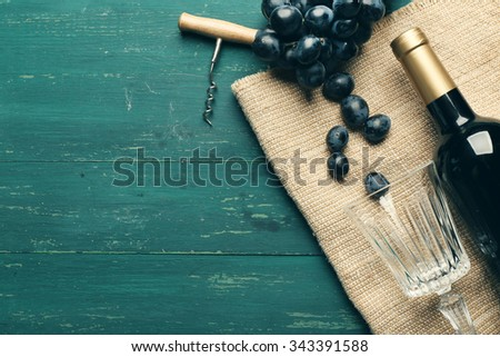 Bottle of wine and grape on wooden table - stock photo