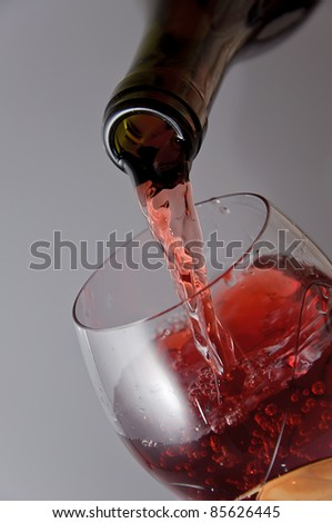 Bottle of wine and wine glass on a grey background