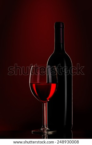 bottle of wine and wine glass on red background - stock photo