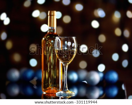 Bottle of wine and wine glass with Christmas decoration on bright background - stock photo