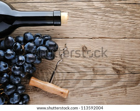 Bottle of wine, corkscrew and grape on wooden background - stock photo