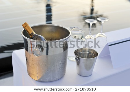 Bottle of wine glasses and pool - stock photo