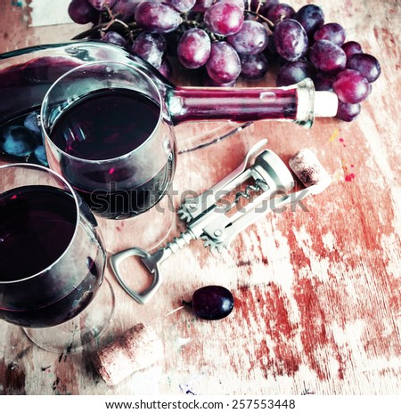 Bottle of wine, grape and corks on wooden table - stock photo