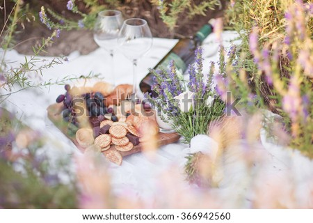 Bottle of wine, grape, cheese and snacks against lavender landscape. Sunset over a summer lavender field in Provence, Crimea. Picnic - stock photo