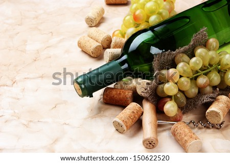 Bottle of wine, grapes and corks on old paper background