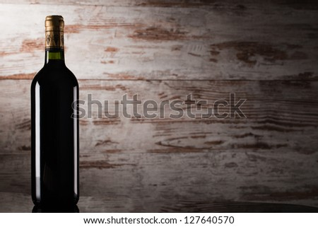 bottle of wine over wooden background - stock photo