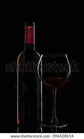 bottle of wine with a glass on a black background