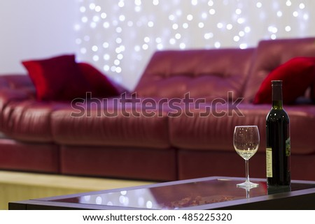 Bottle of wine with a glass on the coffee table on a background of leather sofa, Artifical light