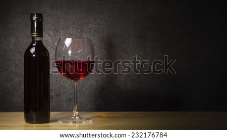bottle of wine with glass of red wine on a wooden table with a grey background - stock photo