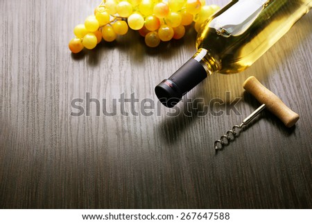 Bottle of wine with grape and corkscrew on wooden background - stock photo