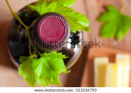 Bottle of wine with green grape leaves and cheese - stock photo