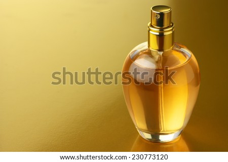 Bottle of woman perfume on gold background. - stock photo