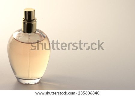 Bottle of woman perfume on light background with copy space. Toned image. - stock photo
