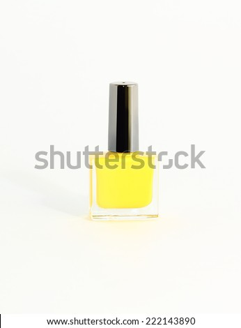 bottle of yellow nail polish on a white background