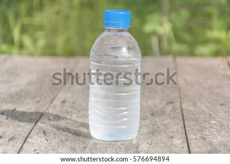 bottle on wooden table texture with nature background.  scene of summer season. Fresh concept.