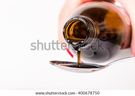 Bottle pouring a liquid on a spoon. Isolated on a white background. Pharmacy and healthy background.  Cough and cold drug. Woman´s hand keep a bottle. - stock photo