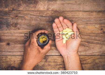 bottle pouring pills on a male's hand - stock photo
