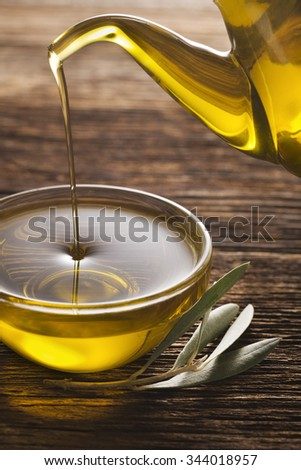 Bottle pouring virgin olive oil in a bowl close up.