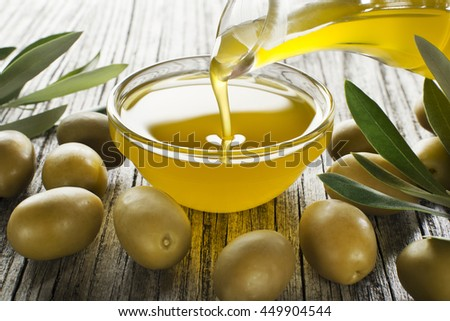 Bottle pouring virgin olive oil in a bowl close up - stock photo