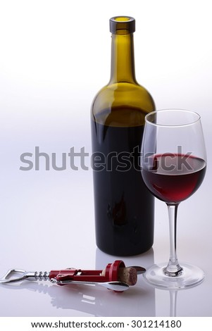 Bottle stylish cork screw and glass goblet full of dessert or rough red wine vinous colour standing together in studio isolated on white and grey background copyspace, vertical picture - stock photo